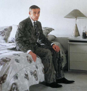 here is mike topp sitting on a bed looking upset, most likely because he just fell into a puddle of ink and ruined his suit