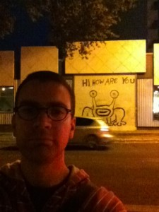 Michael Davidson stands in front of graffiti of a frog by Daniel Johnston